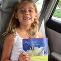 "Sienna, 6 years old, holding her favorite book, ""Peace in the Present Moment."""